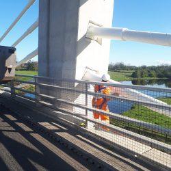 Man in High Vis Working on Exterior of Bridge
