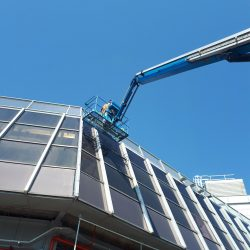 Cherry Picker Raised High Against Windows For Cleaning